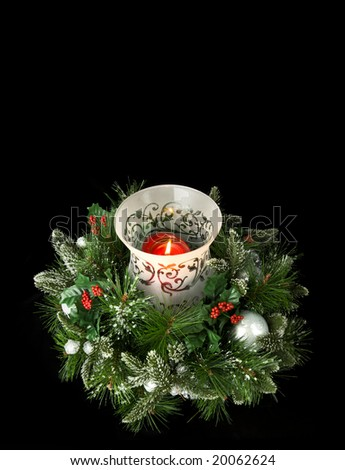 Evergreen centerpiece candle with greenery, isolated on black, lots of room for copy
