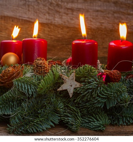 Evergreen fir tree advent garland with burning candles on wooden background
