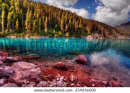 Evergreen trees lining a pure mountain lake with rocks in the foreground.  - stock photo