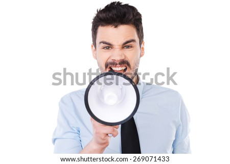 Everybody listen to me! Furious young man in shirt and tie holding megaphone and shouting while standing against white background