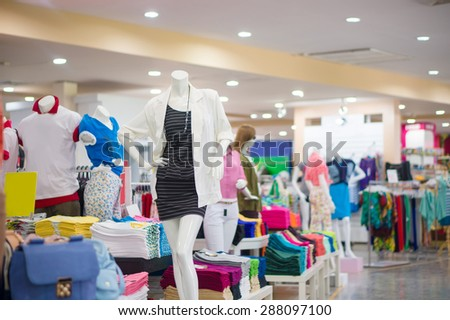Everyday dressed woman mannequin  with black striped dress and white jacket among cloth on back - stock photo