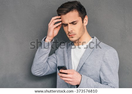 Everyday issues. Pensive young man holding mobile phone and looking at it while standing against grey background - stock photo
