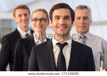 Everyday leader. Confident young man in formalwear looking at camera and smiling while his colleagues standing behind him - stock photo