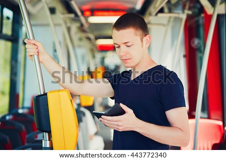 Everyday life and commuting to work by bus (tram). Handsome man is paying transport ticket with mobile phone.  - stock photo