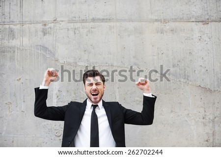 Everyday winner. Happy young man in formalwear keeping arms raised and expressing positivity while standing against the concrete wall - stock photo