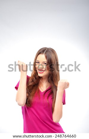 Everyday winner. Happy young smiling caucasian woman keeping arms raised and looking at camera while standing on white studio background - stock photo