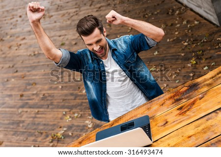Everyday winner. Top view of excited young man keeping arms raised and expressing positivity while sitting at the wooden table outdoors - stock photo