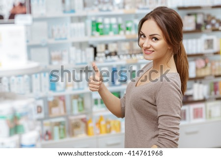 Everything I need here. Portrait of a beautiful female pharmacy customer showing thumbs up. - stock photo