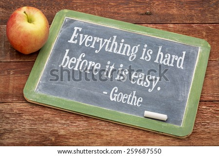 Everything is hard before it is easy - Goethe quote  on a slate blackboard against red barn wood - stock photo