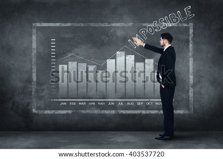 Everything is possible. Full length of confident young man in full suit standing near concrete wall and touching illustrated chart   - stock photo
