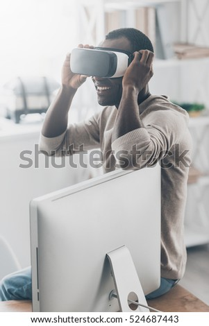 Everything is so real! Handsome young African man adjusting his VR headset while sitting on the desk