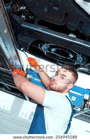 Everything seems to be in order. Low angle image of a handsome muscular car mechanic in uniform working with a spanner on the engine in car service station