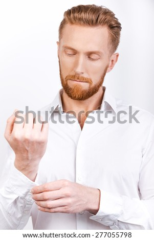 Everything should be perfect. Confident young bearded man adjusting sleeves while standing against white background
