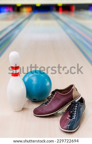 Everything you need for plying bowling. Close-up of bowling shoes, blue ball and pin lying on bowling alley