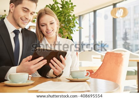 Everywhere connected. Horizontal portrait of two cheerful business colleagues using digital tablet over a cup of coffee at the local coffee shop - stock photo