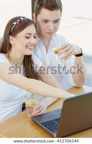 Everywhere connected. Vertical portrait of a beautiful smiling woman showing something on her laptop to her man while sitting together at the cafe - stock photo