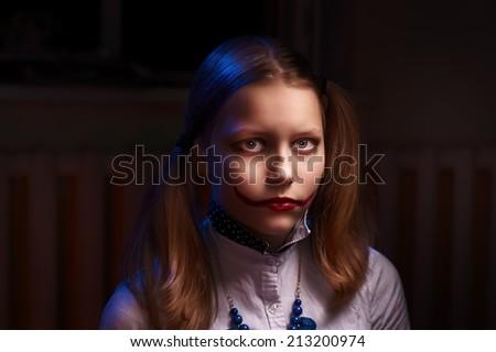 Evil clown teen girl looking at the camera - stock photo
