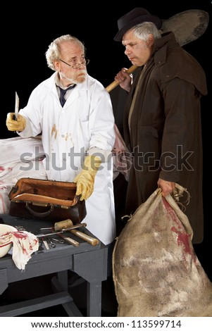 Evil doctor brandishing cleaver exchanges glances with grave robber over bloody corpse. Stage effect, isolated on black background, spot lighting. - stock photo