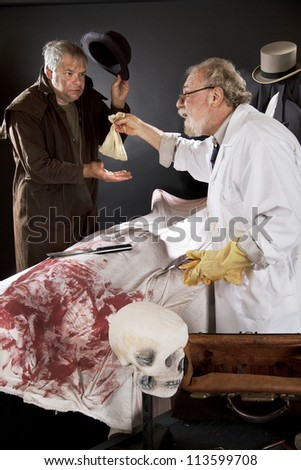 Evil doctor reaches over bloody corpse and pays grave robber, who tips hat. Stage effect with dark background, spot lighting. - stock photo
