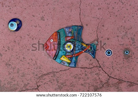 Evil eye amulet on a decorative glass fish to protect from bad things using by turkish culture