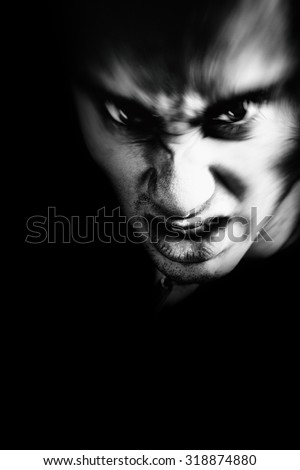 Evil face of scary angry man in the dark - stock photo