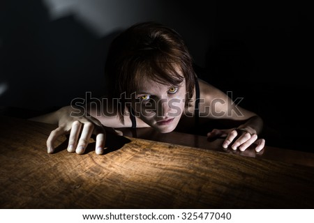 Evil girl with glowing yellow eyes crawling to you from the darkness - stock photo