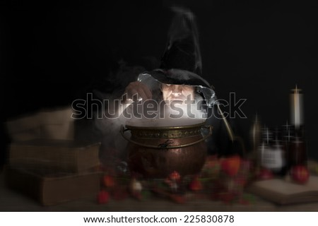 evil halloween witch making a potion in a copper cauldron - stock photo