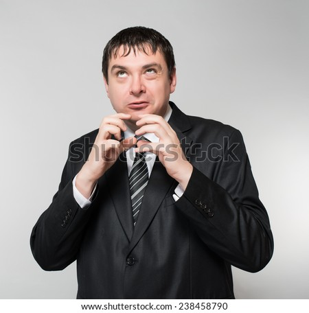 Evil looking businessman clasps his hands under his chin, in dramatic lighting - stock photo