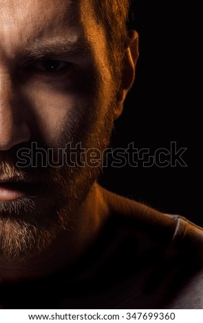 Evil looking man with angry eyes on black background.