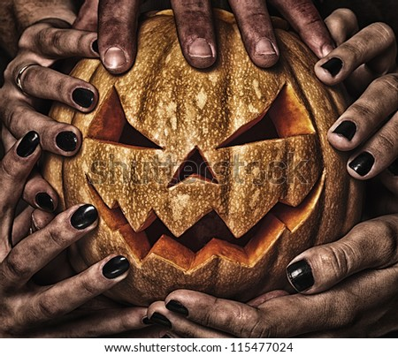 evil pumpkin with glowing eyes that are holding, closeup - stock photo