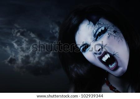 evil vampire woman beautiful halloween over night background - stock photo