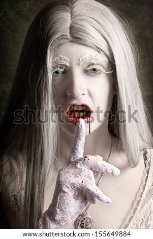 Evil white vampire woman gesturing the quiet of silence on dark interior background. Monster secret