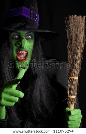 Evil witch and her broomstick, black background - stock photo