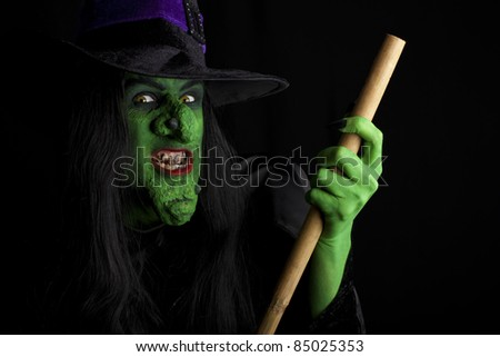 Evil witch flying on her broomstick, black background - stock photo