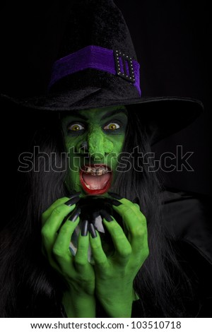 Evil witch holding her crystal ball, black background. - stock photo