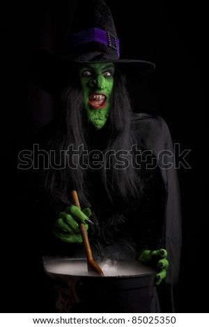Evil witch stirring her misty cauldron, black background. - stock photo