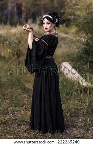 Evil witch woman casting a spooky spell with magic hands. Witchcraft - stock photo