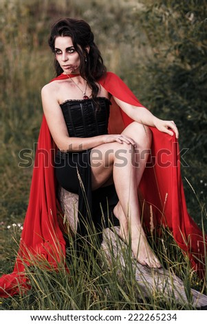Evil witch woman sitting outdoors - stock photo