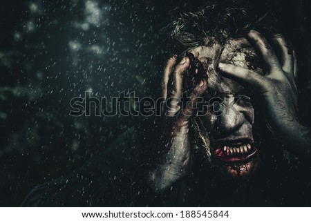 Evil zombie man expressing fear when turning into the living dead at dark haunted forest. Gripping terror - stock photo