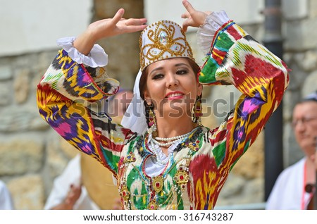EVOLENE, SWITZERLAND - AUGUST 13: Beautiful Uzbekistani dancing girl from Issar in the CIME mountain culture Festival: August 13, 2015 in Evolene, Switzerland