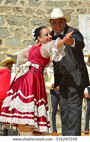 EVOLENE, SWITZERLAND - AUGUST 11: Mexican dancers hand in hand from Guadelupe Omexochitl in the CIME mountain culture Festival: August 11, 2015 in Evolene, Switzerland - stock photo