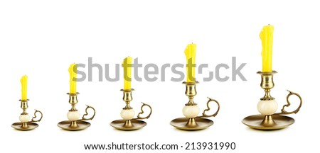 Evolution concept.Old candle holders with candle isolated on white - stock photo