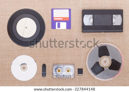Evolution of information carrier from analog to digital. Objects on background from the sackcloth. - stock photo