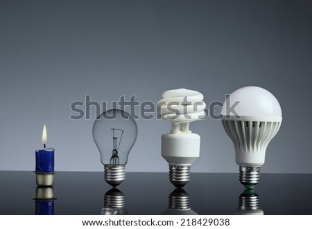 Evolution of light concept, candle, tungsten, fluorescent and LED bulb - stock photo