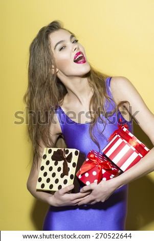 Exalted smiling girl in violet jumpsuit holding colorful boxes of presents standing on yellow background, vertical photo - stock photo