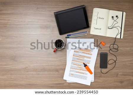 Exam week background, with various study tems, such as a highlighted reader with standard (lorum ipsum) text, a cup of coffee, electronic tablets, music player and ear plugs, and a calendar - stock photo