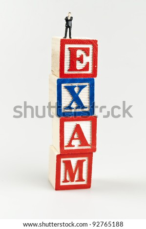 Exam word and toy business man - stock photo