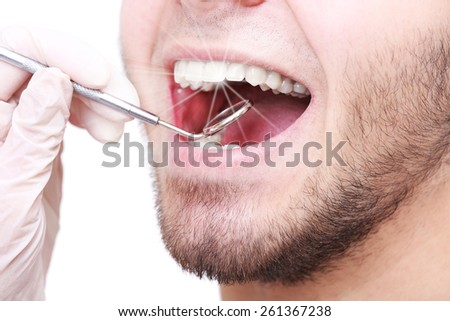Examine of young man by dentist closeup - stock photo
