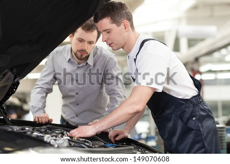 Examining a car. Confident auto mechanic examining car engine while customer looking at it