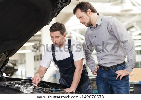 Examining a car engine. Confident auto mechanic showing something on the engine to the car owner